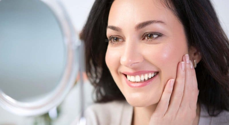 Woman smiling while touching face because her skin feels great after taking a collagen supplement.