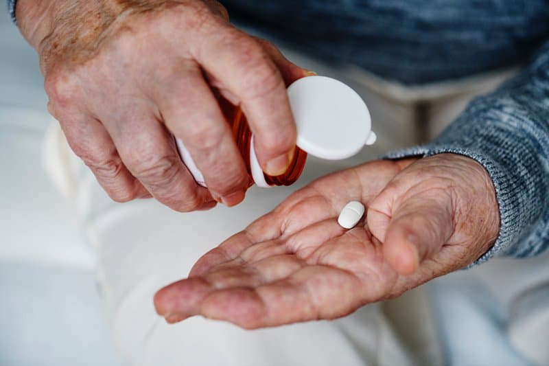 Man holding pill bottle with one pill in palm.