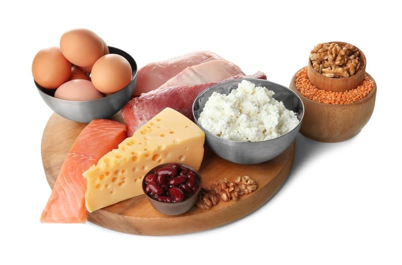 Essential Nutrients: Eggs, salmon, cheese, nuts on wooden plate
