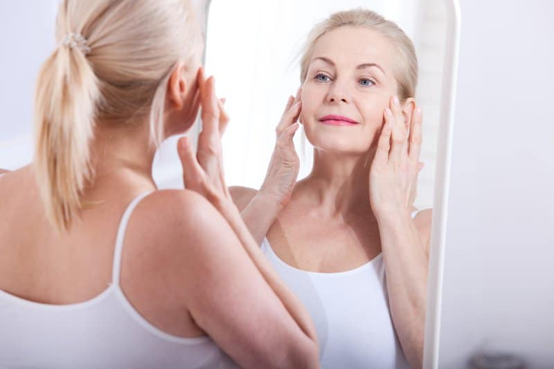 Older lady looking at herself in the mirror and touch her face with her finger tips