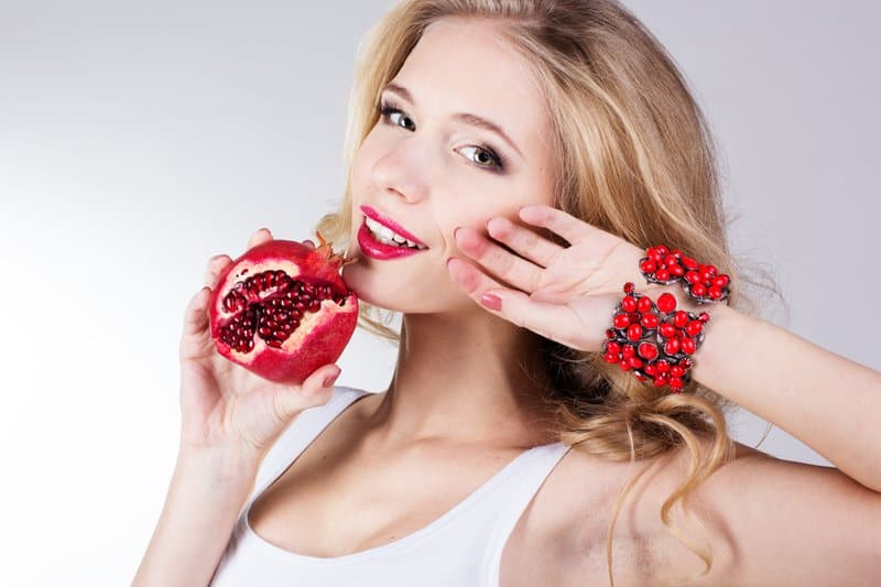 Girl holding a pomegranate in her hand and modeling a bracelet on the other while touching her face.