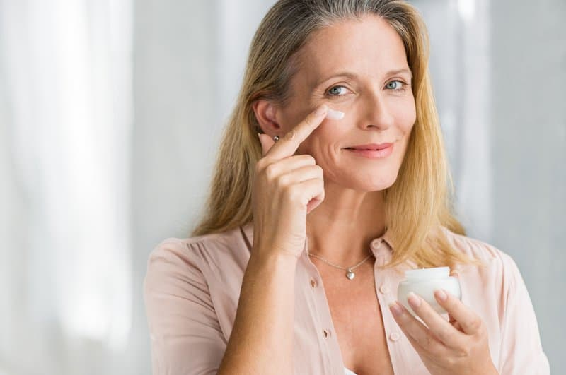 Women putting cream on her face