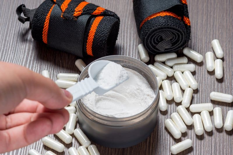 guy scooping creatine powder with creatine capsules on the table