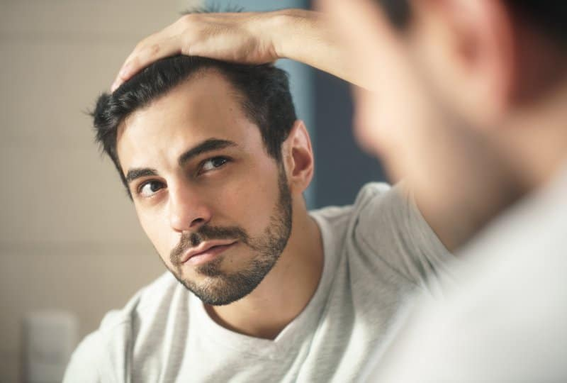 Guy checking in mirror for hair loss