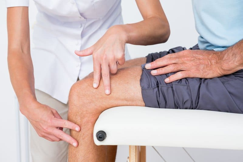 Doctor consulting patient about his knee joints and his joint health.