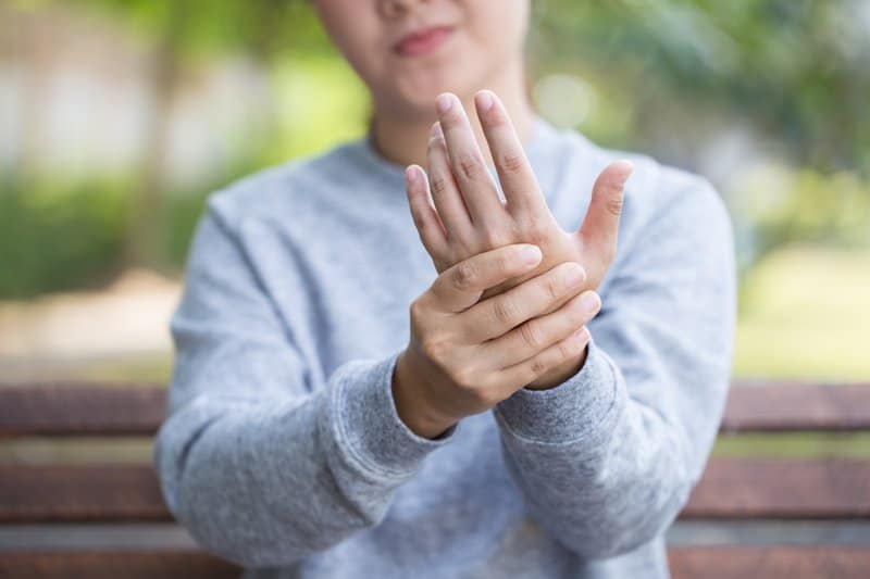 Women feeling the joints in her hand because she feels discomfort.