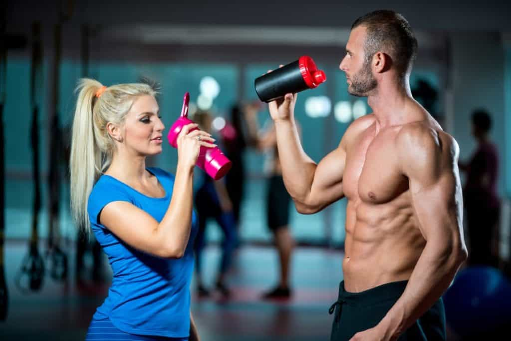 couple drinking muscle supplements at gym