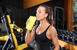 woman drinking pre-workout in gym