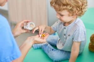 boy taking vitamins for kids