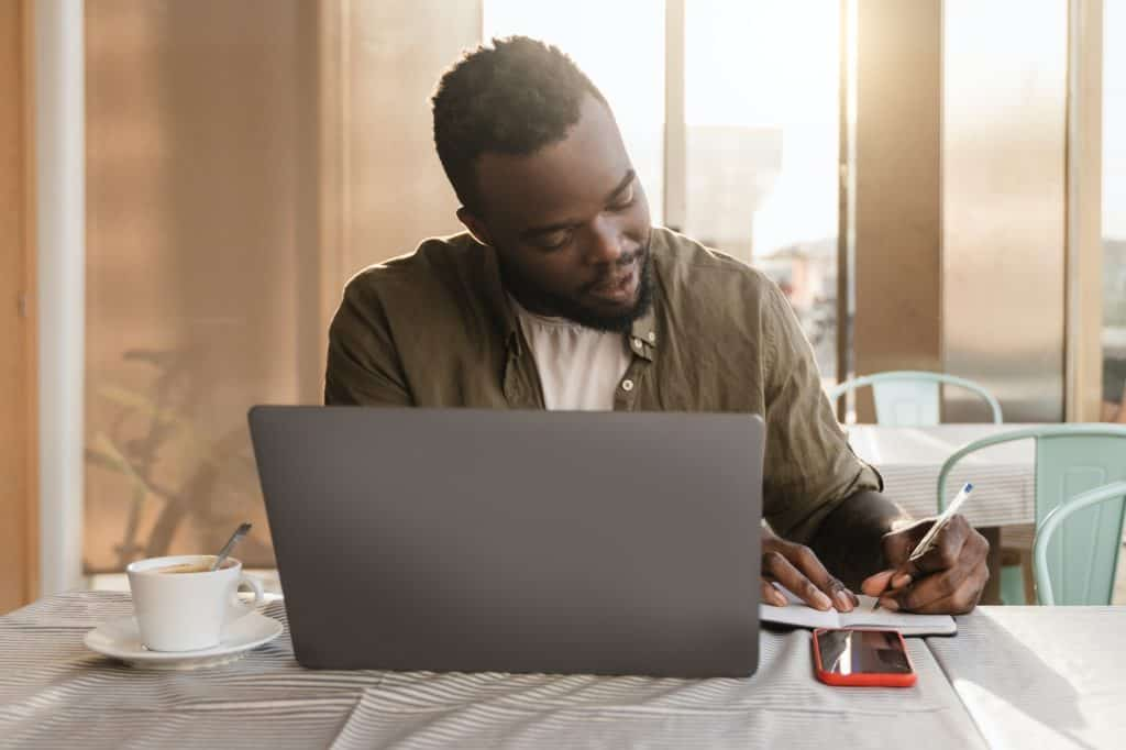 Business african american man using computer laptop working at bar restaurant - Focus on face